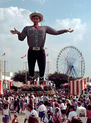 Big Tex stands tall as the crowd mills about at the Texas State Fair.