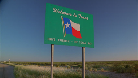 "A green sign on the side of the road reads, ""Welcome to Texas. Drive friendly - the Texas way."""