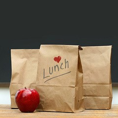 """Three brown lunch bags sit next to a red apple. One brown bag has """"Lunch"""" written on it with a small heart."""